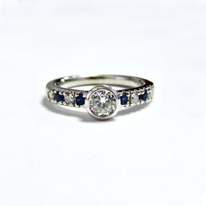 WF 30 - 14K white gold ring with center bezel set diamonds, and sapphire and diamonds on the shoulders.