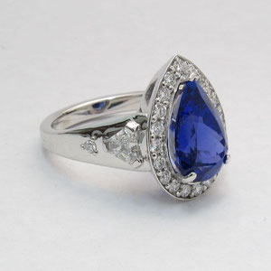 CS 30 - 14k white gold ring featuring a center tanzanite with a halo of diamonds, flanked by clipped corner trillions, and a bead set melee diamond on either side.
