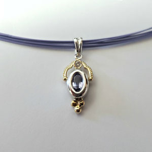 P 107 - 14K two toned pendant with oval tanzanite and diamond accent.