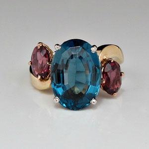 CS 2 - 14K yellow, white, and rose gold bypass ring. The center blue topaz is flanked by rhodolite garnets.