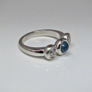 CS 50 - 14K white gold ring with center cabochon sapphire and two diamonds.