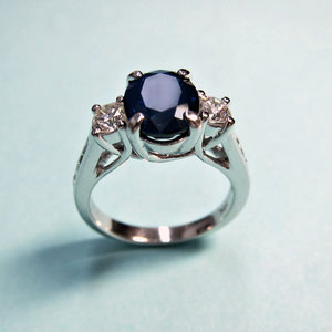 CS 38 - 14K white gold trellis style 3 stone ring with center sapphire and side diamonds.