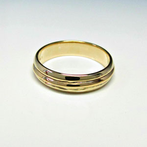 B 23 - 14K yellow gold gents wedding band.  A rose gold family heirloom band has been added to the outside.