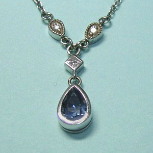 P 20 - 14K white gold pendant with diamonds and bezel set pear shaped sapphire.