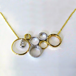 P 70 - 14K two toned necklace with circle designs and a bezel set diamond.