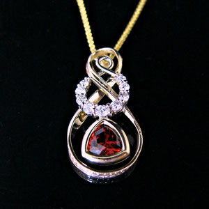 P 97 - 14K two tones pendant with garnet and diamonds.