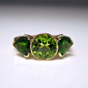 CS44 - 14K yellow gold ring with center peridot and triangle tzavorite garnets.