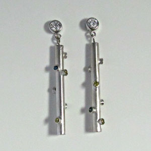 E 34 - 14k white gold bezel set diamond stud featuring drops accented with bezel set blue and yellow diamonds.