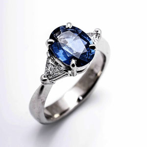 CS 19 - 14k white gold ring with a center oval sapphire and side trillion diamonds.