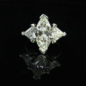 DF 27 - 14K white and yellow gold ring with center marquis diamond and two trillion diamonds.
