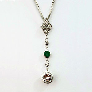 P 80  14K white gold lavalier with diamonds and an emerald.