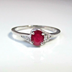CS 23 - 14k white gold bypass ring with an oval ruby and round accent diamonds.