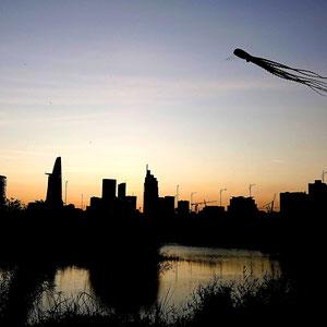 Drachen vor der abendlichen Skyline von Saigon