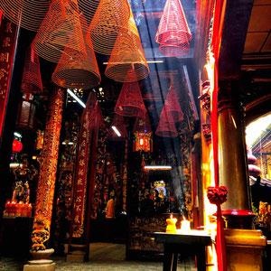 Ein buddhistischer Tempel in Saigon – von den Decken hängen riesige Räucherspiralen und hüllen das Innere in einen magischen Dunst.