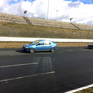 Gegen Mittag bei Sonnenschein, viel Wind und rasch abtrocknender Rennstrecke der Dacia Logan Cup Tourenwagen auf der Zielgeraden