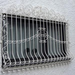 Klassisch verschnörkeltes Fenstergitter in weiß