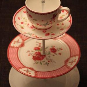 3-stöckige etagère (neues geschirr), in den farben weiss, rot, rosé, mit blumenmuster, ca. h 35 x b 21 cm, weisse verbindungsstangen mit herz, fr. 55.00 - VERKAUFT!