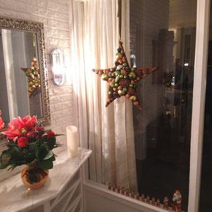 Grün - brauner Stern zwischen Fenster und Spiegel dazu ein Amaryllis Blumenstrauß.