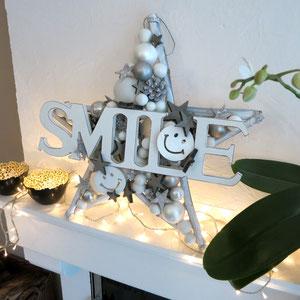Weißer Stern mit SMILE Schriftzug mit Lichterkette auf dem Kaminsims arrangiert.