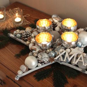 Tischdekoration im Stern Design - silberfarbiger Stern mit vier Windlichtern und XMAS - Schild auf Tannenzweige gelegt.