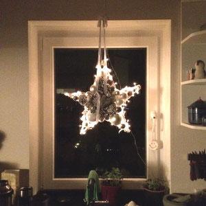 Weiß - grauer Stern mit eingearbeiteter Lichterkette im Küchenfenster