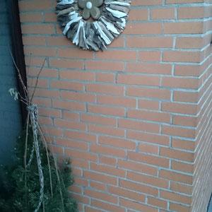 Treibholzsonne vor hellem Klinker im Eingangsbereich