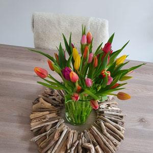 Treibholz Kranz als Tischdekoration mit einem Tulpenstrauß in der Mitte.