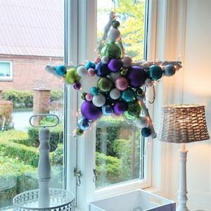 Fensterdekoration bestehend aus einer weißen Stehlampe, Kerzenleuchter und einem Glaskugel Stern in fröhlichen Farben.