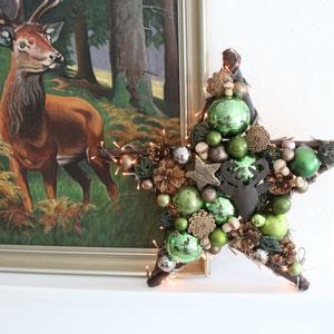 Grün - brauner Stern vor einem Ölgemälde - auf dem ein Hirsch abgebildet ist.