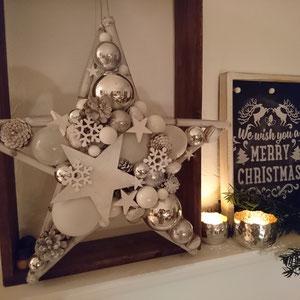 Weißer Stern in winterlichem Design mit Schneeflocken dekoriert und mit Sphärenlicht auf einen Kaminsims gestellt.
