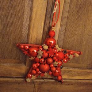 Stern aus roten Glaskugeln und Zapfen an eine Kleiderschranktür gehängt.