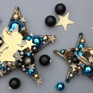 Deko-Sterne in gold - blau - schwarz mit Engel und Feder liegen auf einem grauen Untergrund.