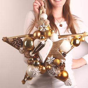 Mädchen mit festlichem Stern in weiß - goldenem Dekor mit weißen Glaskugeln - weißem Holzherz und goldener Feder.