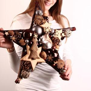 Großer Stern mit Eichhörnchen - braunen Glaskugeln und einem Holz Tannenbaum von einem Mädchen gehalten.