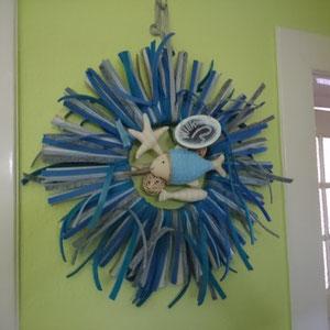 Sonne mit blauen Filzstreifen, Fisch und Willkommenschild im Hauseingang