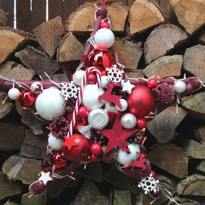 Weiß-roter Stern mit eingearbeiteter Lichterkette an einen Holzstapel gehängt.