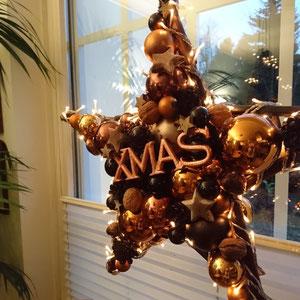 Stern in schwarz - kupfer - braun mit XMAS als stimmungsvolle Fensterdekoration für die Weihnachtszeit.