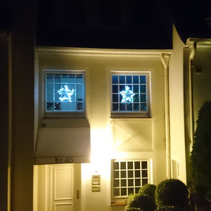 Sterne mit Lichterketten  von außen fotografiert als leuchtende Fensterdekoration.