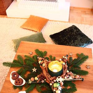 Tischstern mit einem Windlicht in grün  und gold. Mit Tannengrün als Tischdeko gemütlich dekoriert - im Hintergrund flackern Kerzen im Kamin.