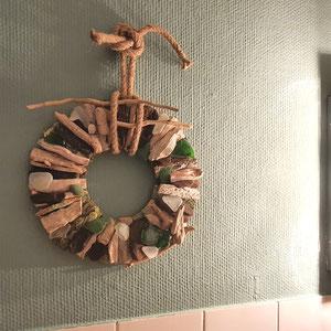 Treibholzkranz an grüner Wand mit Seeglas und Seil Aufhängung