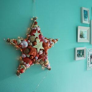 Großer Stern mit Lichterkette in gold-orange-rosa als Wandschmuck an einer mintfarbenen Wand.