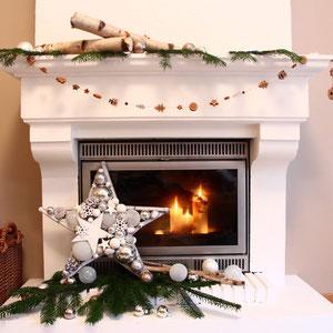 Weißer - 50 cm Stern mit Tannengrün vor dem Kamin dekoriert. Im Kamin brennen weiße Kerzen.