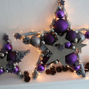 Ein kleiner 30 cm und ein großer Stern in 50 cm in violett - grau zusammen arrangiert. Beide Sterne sind mit grauen Holzsterne geschmückt.