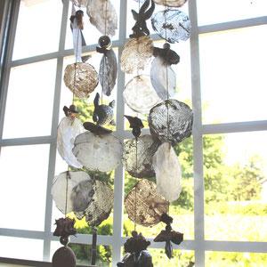Windspiel als Sichtschutz aus silberfarbenen und weißen Capiz Muscheln.