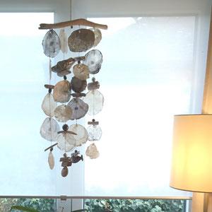 Klangspiel aus silbernen und weißen Muschelscheiben mit maritimen Accessoires.
