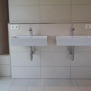Hinter der Waschbeckenwand versteckt sich die begehbare Dusche