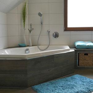 Neben der Badewanne befindet sich eine gemauerte Sitzbank