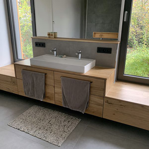 Moderner Material-Mix mit Feinsteinzeugfliesen in Betonoptik und warmen Holz.