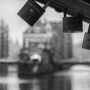 Die Hamburger Speicherstadt verschwimmt hinter ein paar der zahlreichen Liebesschlösser an der Poggenmühlenbrücke