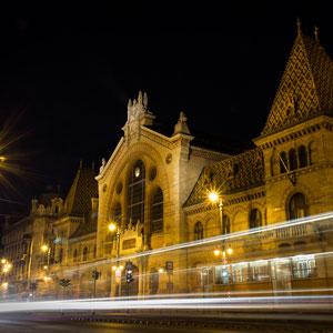 Die große Markthalle in Budapest, Ungarn, aus dem späten 19. Jahrhundert mit den Lichtern der vorbeifahrenden Autos